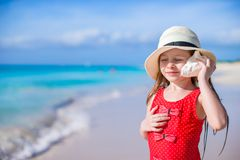 Liten gullig flicka med snäckskalet i händer på den tropiska stranden Royaltyfri Fotografi