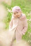 Liten gullig flicka nära ett blomningträd Royaltyfria Foton