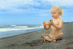 Liten gullig flicka på havsstranden som äter den mogna papayaen Royaltyfria Bilder