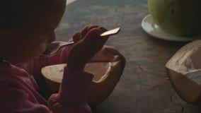 Liten gullig flicka som äter kokosnöten vid skeden på kafét med seaview i ultrarapid arkivfilmer