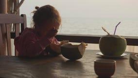 Liten gullig flicka som äter kokosnöten vid skeden på kafét med seaview i ultrarapid lager videofilmer