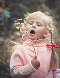 Liten gullig flicka som blåser maskrosen arkivbilder