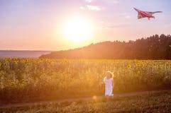 Liten gullig flicka som flyger en drake Fotografering för Bildbyråer