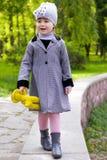 Liten gullig flicka som går med en leksak i hand Arkivfoto