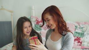 Liten gullig flicka som ger gåvaasken till hennes unga lyckliga mamma som hemma firar sammanträde för moderdag på säng i hemtrevl arkivfilmer