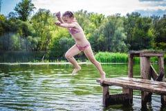 Liten gullig flicka som hoppar av skeppsdockan in i en härlig flod på solnedgången arkivfoto