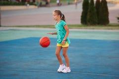 Liten gullig flicka som spelar basket utomhus Arkivbild