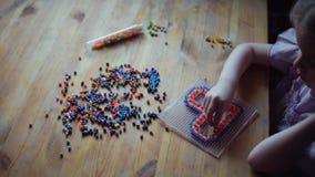 Liten gullig flicka som spelar med den f?rgrika mosaiken