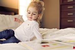 Liten gullig flickaläsebok på säng royaltyfri fotografi