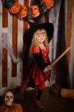 Liten gullig halloween häxaflicka på kvasten arkivbild