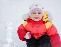Liten gullig le flicka som gör en snögubbe arkivfoton
