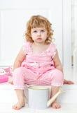 Liten gullig lockig flicka i en rosa klänning med prickar som sitter på den vita farstubroProvence stilen Arkivfoton