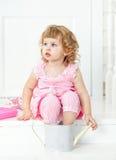 Liten gullig lockig flicka i en rosa klänning med prickar som sitter på den vita farstubroProvence stilen Royaltyfri Bild