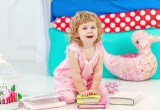 Liten gullig lockig flicka i rosa pyjamas som håller ögonen på boksammanträdet på golvet i barnens sovrum arkivbilder