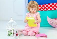 Liten gullig lockig flicka i rosa pyjamas som håller ögonen på boksammanträdet på golvet i barns sovrum arkivfoton