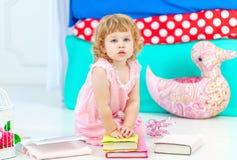 Liten gullig lockig flicka i rosa pyjamas som håller ögonen på boksammanträdet på golvet i children&en x27; s-sovrum royaltyfri bild