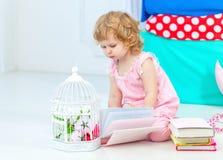 Liten gullig lockig flicka i rosa pyjamas som håller ögonen på boksammanträdet på golvet i children& x27; s-sovrum arkivbild