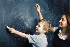 Liten gullig pojke i exponeringsglas med den unga verkliga läraren, klassrum som studerar på svart tavlaskolakidoen royaltyfria foton