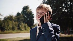 Liten gullig pojke i samtal för affärsdräkt och bandpå telefonen