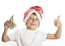 Liten gullig pojke i santas den röda hatten som isoleras med Arkivfoton