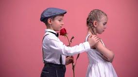 Liten gullig pojke med den röda rosen som ber om ursäkt till den kränkta flickvännen, första förälskelse royaltyfri foto