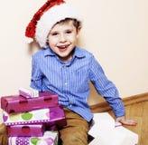 Liten gullig pojke med julgåvor hemma slut upp emotionellt Arkivfoto