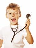 Liten gullig pojke med stetoskopet som spelar som vuxet le för yrkedoktorsslut som upp isoleras på vit Royaltyfri Foto