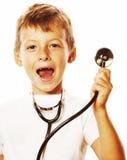 Liten gullig pojke med stetoskopet som spelar som vuxet yrke D Arkivfoton