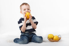 Liten gullig pojke som äter ett gult äpple på vit bakgrund Royaltyfri Fotografi