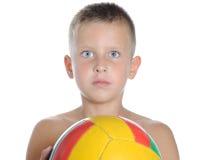 Liten gullig pojke som spelar den isolerade fotbollbollen royaltyfri fotografi