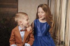 Liten gullig pojkeflicka som kramar att spela på vit bakgrund, lyckligt familjslut som isoleras upp le för brodersyster royaltyfria foton