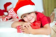 Liten gullig unge i santas den röda hatten royaltyfri bild