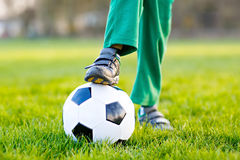 Liten gullig ungepojke av spela fotboll 4 med fotboll på fält, utomhus fotografering för bildbyråer