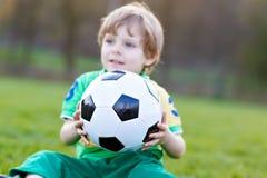 Liten gullig ungepojke av spela fotboll 4 med fotboll på fält, utomhus Royaltyfri Foto