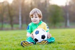 Liten gullig ungepojke av spela fotboll 4 med fotboll på fält, utomhus Arkivbilder