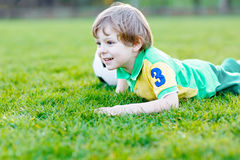 Liten gullig ungepojke av spela fotboll 4 med fotboll på fält, utomhus Royaltyfria Foton