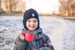 Liten gullig ungepojke med koppen av kokhet choklad eller childr Arkivbild