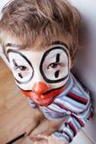 Liten gullig verklig pojke med facepaint som clown Royaltyfria Bilder