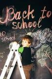 Liten gullig verklig pojke på svart tavla i klassrum, tillbaka till skolabegreppet Royaltyfria Bilder