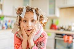 Liten häpen flicka med papiljotter på hennes huvud arkivfoton