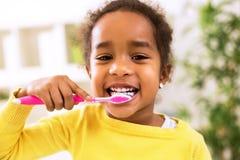 Liten härlig afrikansk flicka som borstar tänder Arkivfoto