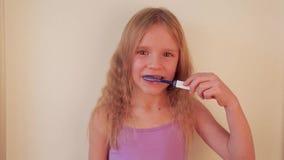 Liten härlig blond flicka som borstar tänder, sunt begrepp lager videofilmer