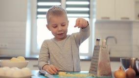 Liten härlig caucasian pojke med stora blåa ögon som lagar mat i det ljusa köket Han är häller ost Ostrivjärn arkivfilmer