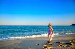 Liten härlig flicka i en klänning och solglasögon arkivfoto