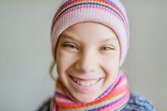 Liten härlig flicka i vinterhatt och halsduk Arkivbild