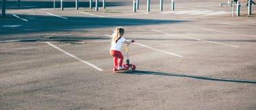 Liten härlig flicka som rider en sparkcykel royaltyfria foton