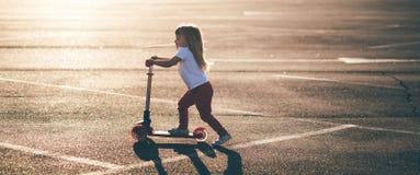Liten härlig flicka som rider en sparkcykel fotografering för bildbyråer