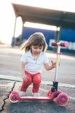 Liten härlig flicka som rider en sparkcykel arkivfoto