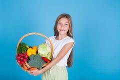 Liten härlig flicka som rymmer en korg av ny frukt och sund mat för grönsaker royaltyfri bild