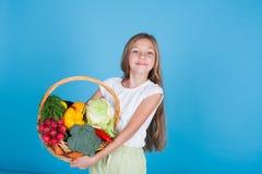 Liten härlig flicka som rymmer en korg av ny frukt och sund mat för grönsaker arkivbild